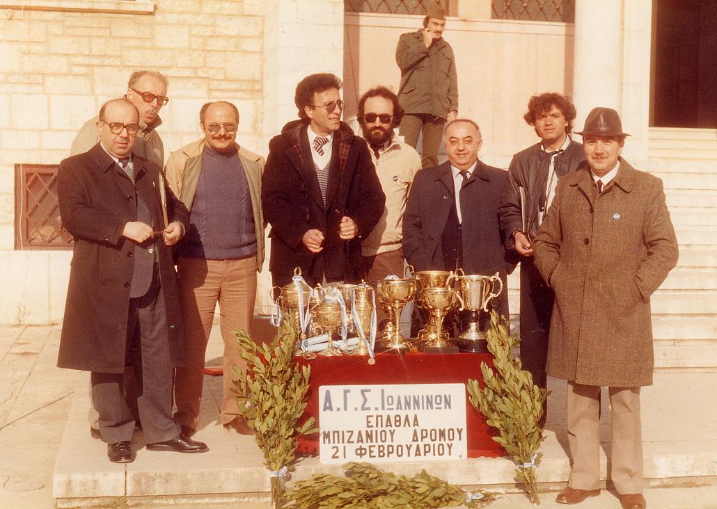 Τα μέλη της Οργανωτικής Επιτροπής και του Διοικητικού Συμβουλίου του Α.Γ.Σ.Ι., μπροστά από την είσοδο του Νομαρχιακού Μεγάρου και πίσω από το τραπέζι με τα έπαθλα για τους νικητές του ετήσιου Μπιζάνιου Δρόμου. Από αριστερά προς τα δεξιά εικονίζονται οι Στράτος Τσόκος, Ανάστασιος Φιλίππου, Ντίνος Γαλάνης, Λουκάς Παπαλουκάς (Γ.Γ. Πανεπιστημίου Ιωαννίνων), Ευάγγελος Λέκκος (πρώην πρωταθλητής άλματος σε ύψος), Σπυρίδωνας Μπαλτογιάννης (πρόεδρος Α.Γ.Σ.Ι.), Κωνσταντίνος Καμπέρης (γυμναστής),, Νικόλαος Ζήκος.